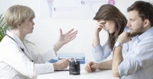Image of sorrowful young marriage at gynecologist's office